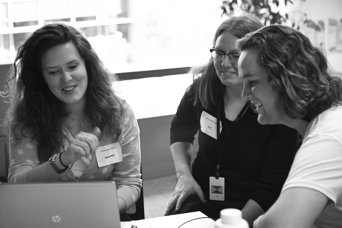 Photograph of civic hackers discussing a project at the OpenAustralia Hackfest 2014